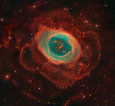 "Heralded as the most famous celestial band -- second only to the rings of Saturn -- the Ring Nebula (also categorized as M57) glows with impressive ""looping structures,"" in a way that looks stunningly like a giant blooming flower floating in space. Luckily for us, the Hubble Space Telescope captured an image in beautiful detail, considering the Ring Nebula exists 2,000 light years away from Earth."