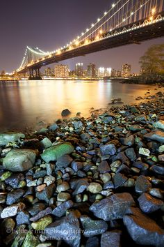 A night photograph of the Manhattan Bridge with a lit up foreground of stones