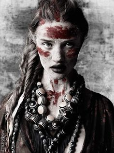 A photograph of a model dressed in tribal clothing. I like the dark colours as it makes the red tribal markings on her face stand out.