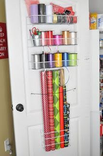 """Gift wrap storage """"used small plastic and foil storage organizer from W-M; elastic with 3m tabs to hold the gift wrap in place; large organizer from Home Depot for the ribbon spools; small metal bucket for scissors, tape, pens and gift tags."""""""