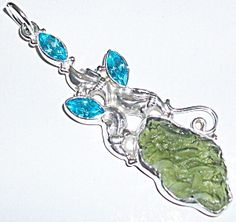 "$124.00 on sale! Moldavite pendant Sterling Silver with Blue Topaz.   Genuine sterling silver, moldavite, blue topaz.  Country of Origin: Czech Rep.  Manufacturer: Artisan Handcrafted  2.3/8""long entirely. Genuine free form moldavite stone is approx. 1"" x 1/2"". Blue topaz accent stones are marquise cut."