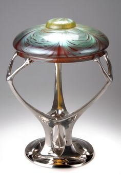 German Art Nouveau polished pewter table lamp with a Loetz glass shade, designed by Friedrich Adler, manufactured by Walter Scherf in Nürnberg under the trade name Osiris, circa 1901-02. Measures 49 cm. high.     SOLD $13,395 May 2004 *At auction time this was the only known example of this lamp and shade combination.
