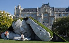 """""""Hungarian artist Ervin Herve-Loranth has unleashed a giant on the city of Budapest. Entitled Feltépve (""""Ripped up"""" or """"Pop Up""""), the cranky colossus is made of polystyrene and appears to be emerging from a secret subterranean lair beneath Szechenyi Square. He was created for Art Market Budapest, a 4-day-long international contemporary art fair."""" - Ellen Kushner"""
