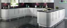 White gloss units with purple glass splashback, black gloss worktop and grey floor.