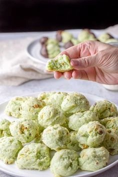 A hand holding one of the pistachio cookies with a bite taken out of it
