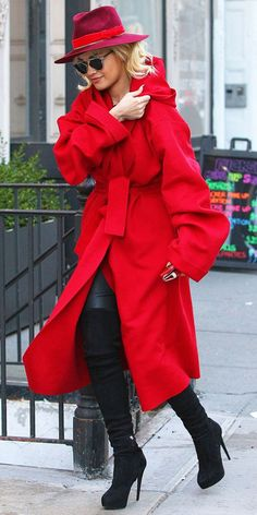 Rita Ora stepped out in a bright red belted coat, Dior sunglasses, red fedora, and thigh-high black boots.