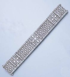 A DIAMOND BRACELET  The articulated openwork band, composed of old mine and single-cut diamond navette-shaped links, segmented by three similarly-set quatrefoil panels, to the old mine-cut diamond border, circa 1920, 16.7 cm.