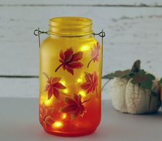 Autumn leaves Mason jar lantern. A quart-sized Mason jar was tinted yellow and orange and then autumn leaves were hand painted onto the jar. A Mason jar hanger was attached to the jar. A string of LED moon lights provides the glow for the lantern. The battery pack requires two coin batteries (included) which are replaceable for a longer glow time.
