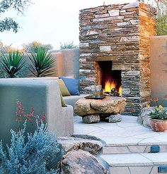 What a romantic and cozy outdoor fireplace and sitting area. Love the stones! I'd have to move far from Texas though to enjoy this kind of outdoor ambiance.