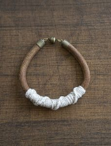 I love bracelets and cuffs. it's always a part of my wardrobe. here's a good find..    handwoven & leather braclet in cream. by kate miss