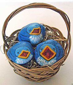 Three stones were transformed into baby bluebirds by applying shades of blue acrylic paint. The hungry little critters are nestled in a small basket.
