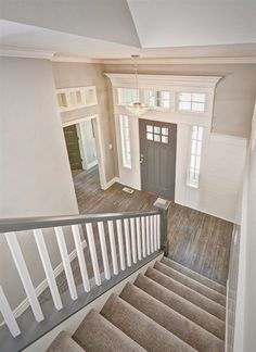 Entryway with gray stair rail and white ballusters. Tuftex carpet with Manningtons Restoration Collection laminate flooring in Black Forest Oak fumed. Benjamin Moore Kendal Charcoal front door with White Dove trim. Transom windows above door frames. Style At Home, Window Above Door, Entry Chandelier, Escalier Design, Transom Windows, Home Reno, My Dream Home, Dream Homes, Home Fashion