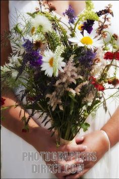 wild flowers for a navy wedding | bride holding wedding bouquet of wild flowers stock photo