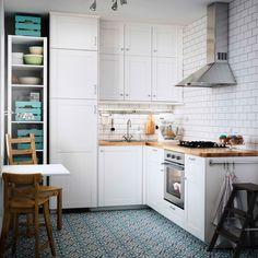 Mala bijela kuhinja s radnim pločama od hrasta. U kombinaciji s pećnicom od nehrđajućeg čelika i napom.