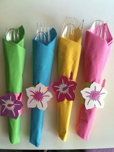 Luau party napkins. To bright colored napkins and wrapped silverware in them. Took a little strip of colored paper and attached it around the napkin. Use my cricut machine and used the Life's a beach cartridge for the flowers.