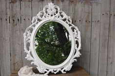 Hand painted, ornate mirror done in soft cottage white, with a protective coating. The mirror has a picture wire hanger. Perfect for wedding, photo prop, shabby chic, nursery or cottage decor. The mir