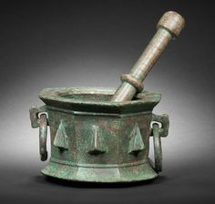 A Seljuk bronze Mortar and Pestle   Persia, 11th/ 12th Century  the mortar of octagonal form with flattened rim and flared foot, two sides with lion's head suspension loops with ring handles, the remaining six with triangular bosses, the pestle of flaring elongated form with ribbed handle and bulbous finial   the mortar 18 cm. diam