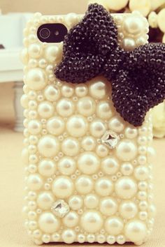 A iPhone case that has white beads and a bow on it