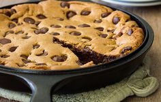 A giant cookie baked in a cast iron skillet, complete with melted chocolate and a gooey center.
