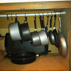 A tension rod in a cabinet with kitchen pots and skillets hanging from it with room below for storage