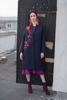 A coat to warm your blues. Constructed on an A-line oversized cut from fashion neoprene and lined with viscose, it fastens in front with a single button for a deep V opening. It is detailed with a handmade asymmetric silk ribboned pattern in coral, blue and bronze hues. The mid-length allows for easy and diverse styling. #viktoriavarga #viktoriavargabudapest #designer #hungariandesigner #blue #coat #handmade #ootd #outfit Layered Fashion, Coral Blue, Silk Ribbon, Mid Length, Blues, High Neck Dress, Bronze, Ootd, Deep