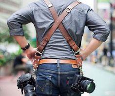 "Strap up for wedding season with the dual camera holster and get two times the photography done. This stylish chestnut colored harness is worn in an ""X"" pattern across the back and leaves both cameras at hip length so you can easily switch between cameras."
