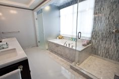 The bigger apartments have this master bathroom, with the toilet in the booth enclosed by smoked glass.