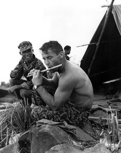 """U.S. soldier in Vietnam plays a Vietnamese flute, to the amusement of a Vietnamese soldier guarding the outpost on Black Virgin Mountain."" U.S. Army photo."