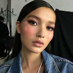 Fresh makeup with blush, pink lips and slicked back hair