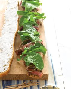 Grilled Steak Sandwiches with Goat Cheese and Arugula: Grilled red onion, goat cheese, grainy mustard, and arugula give these steak sandwiches an elegant spin. Assemble on two baguettes to serve eight people.