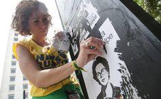 São Paulo - Mulher retira cartaz na avenida Paulista antes do início do protesto contra a presidente Dilma
