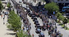 Muhammad Ali's funeral procession passes as onlookers line the street. AP Photo