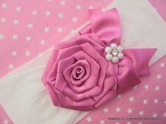 Faixa para bebê em meia de seda.  Rosa de fita de cetim.  A rosa mede…