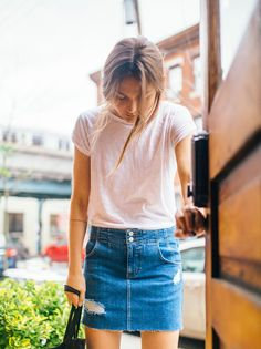 Corsette Mini Skirt | Denim mini skirt featuring allover distressing detailing and a raw hem.    * Super stretch denim   * Adjustable buckle in back   * Five-pocket style   * Zip fly