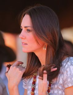 Catherine, Duchess of Cambridge touches her hair as she looks on at the National Indigenous Training Academy on April 22, 2014 in Ayers Rock, Australia. The Duke and Duchess of Cambridge are on a three-week tour of Australia and New Zealand, the first official trip overseas with their son, Prince George of Cambridge.