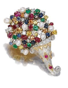 GOLD, DIAMOND, RUBY, EMERALD, SAPPHIRE, TOURMALINE, CULTURED PEARL BROOCH, CAZZANIGA Shaped cornucopia adorned with a mosaic of diamonds, pearls and colored stones of varying sizes, the basic two-tone gold engraved decoration, dotted with round rubies.
