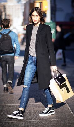 Alexa Chung wears a gray sweater, black coat, skinny jeans, and Vans sneakers