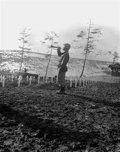 """Marine Cpl. Charles E. Price sounds """"Taps"""" over the graves of fallen Leathernecks during memorial services Dec. 13, 1950, at the 1st Marine Division cemetery at Hungnam, Korea, following the division's break-out from the Chosin Reservoir. (DoD Photo by Cpl. W.T. Wolfe, USMC.)"""