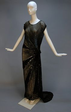 TRAINED BEADED and SEQUINNED GOWN, c1930. Black net tabard style with open side to the waist (nice) and on left side of skirt, having a sunburst of large and small black sequins and bugle beads.