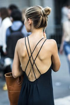 On the street: Open back criss-cross mini dress and brown handbag.