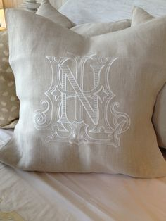 """Vintage"" monogram in white thread on a Libeco Natural 20"" Pillow ""Bluebell"" font combined with ""Lindley"" in gold thread on a Sferra..."