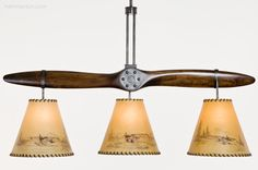 This bar light designed for a recreational pilot makes clever use of a vintage Cub aircraft propeller. The rawhide shades feature hand-inked drawings of three different vintage airplanes. Custom Lighting, Bar Lighting, Aircraft Propeller, Lighting Manufacturers, Vintage Airplanes, Pilot, Clever, Shades, Lights