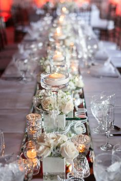 Mirrors the length of the tables + Mercury Glass + Floating Candles + White Flowers (and warm lighting) .. Very Romantic. See more of this wedding on SMP: http://www.StyleMePretty.com/little-black-book-blog/2014/03/07/irish-barn-glam-wedding-at-whistling-straits/ Heather Cook Elliot Photography