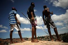 Brazilian drug gang members pose with weapons atop a hill overlooking a slum in Salvador, Bahia State, April 11, 2013. (Lunae Parracho/Reuters).