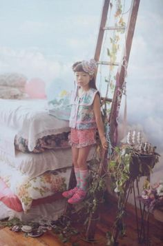 Fafa creates a whimsical wonderland with soft photography, sky wallpaper, and quirky printed clothes. Crafty cut-out stars, balloons and a stack of floral printed cots decorate the set. Girly printed dresses and separates complement the sweet set. (Spring Summer 2013)