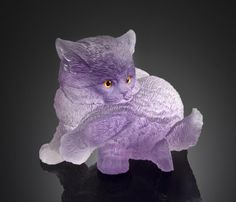 Amethyst Carving of a Kitten Alfred Zimmerman Idar-Oberstein, Germany Depicting a kitten grooming his leg, carved from a single large crystal of fine transparent violet amethyst, realistically textured to suggest the fur. Weighing approximately 1135 carats. Length 3 1/4 in