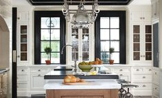 Fabulous kitchen with windows accented with black moldings flanking glass-front cabinet as well as black tray ceiling punctuated with pot rack with integrated glass pendant lighting over kitchen island with black countertop lined with DWR Precision Stools next to drop-down baking island with white marble top.