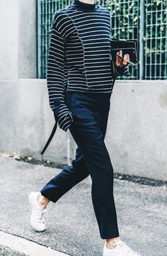 A striped sweater is worn with navy blue trousers and white sneakers