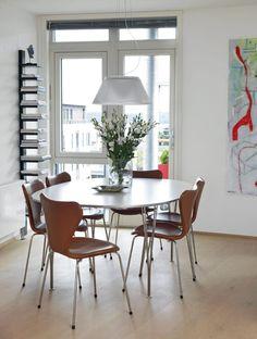 Spisestuen er innredet i en moderne stil, med lyse farger. Fargen på stolene rundt spisebordet tilfører varme i rommet.