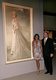 Princess Stephanie and Prince Albert standing next to a portrait of Princess Grace.